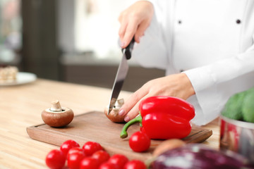 Female chef cutting vegetables in kitchen, closeup