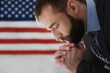 Man praying on American flag background