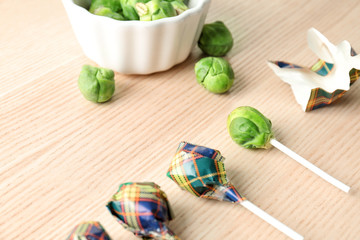 Brussel sprouts with lollipop sticks in candy wrappers on table. April fools food Wall mural