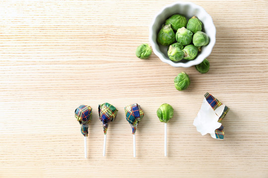 Brussel sprouts with lollipop sticks in candy wrappers on table. April fools food