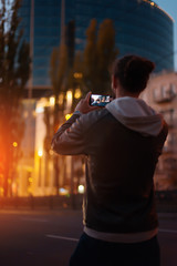 Urban photographer with mobila phone make photo on street. The guy photographed an evening city on the phone. Photos and low keys and with a soft focus.