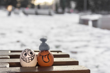 chicken eggs with cheerful faces sitting on a bench