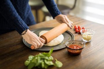 Female hands preparing pizza dough