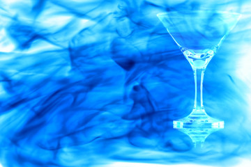Empty the cocktail glass enveloped in blue smoke.