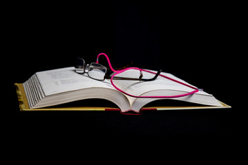 Book with Glasses on Black Background