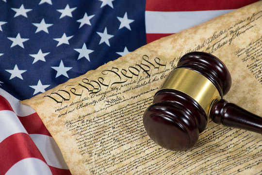 wooden court gavel on United States Constitution document and American flag