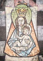 Fototapete - Virgin Mary with baby Jesus painted on a wall of the ancient cemetery of San Candido.