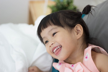 Happy Asian child girl smile on the bedroom.