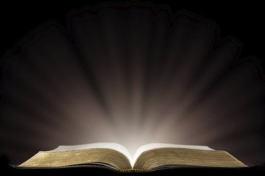 A Book that looks like a Bible Open in a Dark Room with Light Pouring Out of it representing enlightment