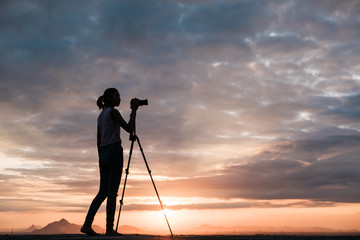 silhouette of Asian women photography with mountain at sunset .