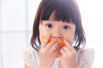 The lovely little girl is eating an orange