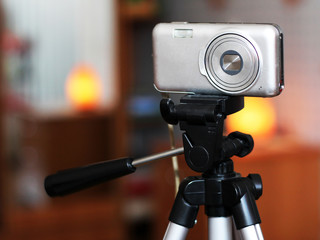 The image of video camera under the tripod in the interior