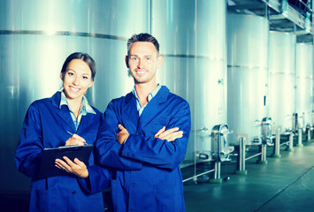 Two young winery professional standing in protective uniform