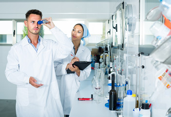experts making tests in winery laboratory.