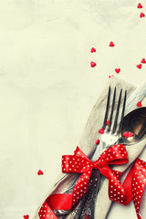 Festive table setting for Valentines Day, set of cutlery, red ribbon and sweet hearts, gray background, top view