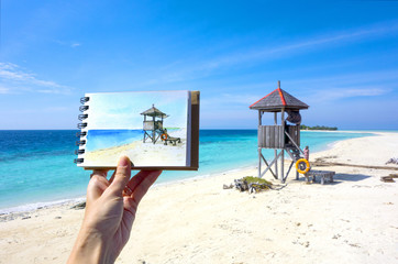 Hand of artist holding Watercolor picture of lifeguard tower or observation tower on tropical beach with clear blue sea. Artist practicing painting watercolor seascape outdoor. Concept for hobby time.