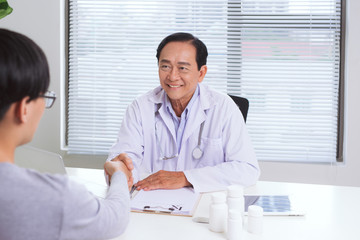 Asian male doctor and patient in the office shaking hands, healthcare and assistance concept