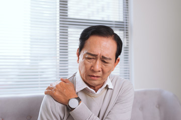 Elderly man suffering from shoulder pain sitting on a sofa in the living room