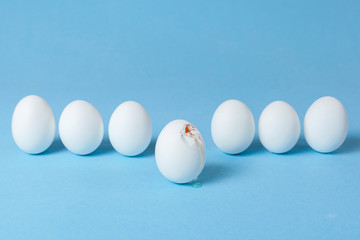 Lot of white eggs from which one is broken with a crack through which the yolk is seen. Blue background