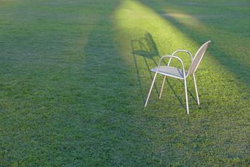 Weißer Gartenstuhl auf Rasen bei niedrig stehender Sonne