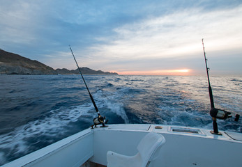 Sunrise view of fishing rod on charter fishing boat on the Pacific side of Cabo San Lucas in Baja MEX BCS