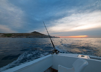 Sunrise view of fishing rod on charter fishing boat on the Pacific side of Cabo San Lucas in Baja California MEX BCS