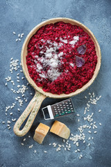 Risotto with beetroot served in a frying pan over blue stone background, top view, vertical shot