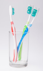 colorful toothbrushes in a glass on background.