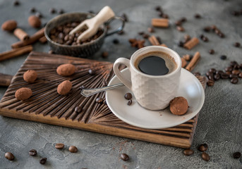 Black coffee with candies on a concrete background