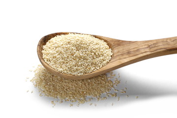 Pile sesame seeds in wooden spoon isolated on white background