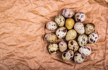 Fresh quail eggs on brown wrapping paper. Dietary products. Organic fresh eggs. Copy space