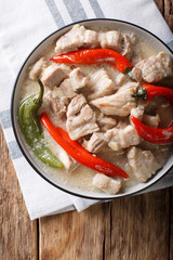 Bicol Express with red and green chili close-up in a bowl. Vertical top view