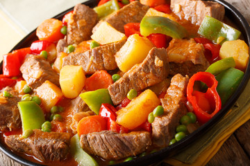 Slow cooked beef with potatoes, peppers, peas, tomatoes and carrots in a spicy sauce close-up. horizontal