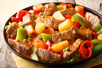 Organic food: beef with potatoes, pepper, peas, tomatoes and carrots in a spicy sauce close-up on a plate . horizontal
