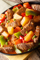 Stew beef with potatoes, peppers, peas, tomatoes and carrots in a large ally on a plate on the table. vertical