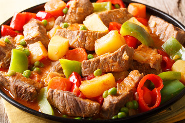 Philippine cuisine: kaldereta beef with vegetables close-up. horizontal