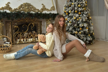 sister of a teenager and boy with a teddy bear at a Christmas tree