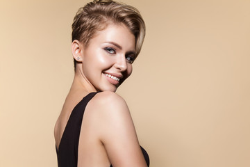 Young smiling woman with modern short hairstyle, studio portrait. Smiling cute female model, close up portrait, isolated on white. Concept of glamour, beauty and fashion.