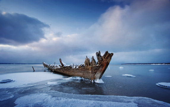 Old wooden shipwreck in ice at sea. Winter on the water at night