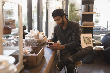 Man using mobile phone while having cup of coffee
