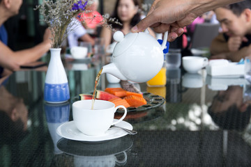 Waiter pouring tea from tea pot with fruit salad on table