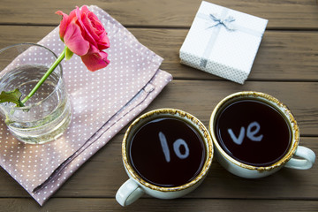 The word love is reflected in two cups of coffee. Valentine's Day Concept