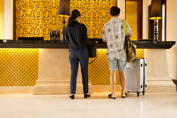 Unidentified tourist couple chek in at reception