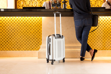Woman tourist with suitcase chek in at reception