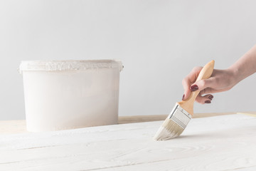 cropped image of woman painting wooden surface with white paint
