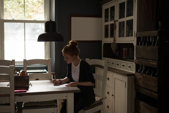 Young woman sitting at table writing a letter