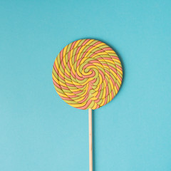 Colorful spiral lollipop on blue background