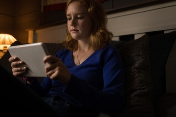 Woman sitting on sofa using her tablet