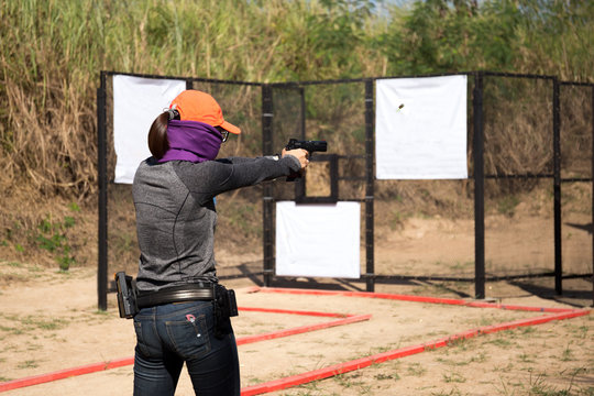 Woman aiming pistol in shooting range