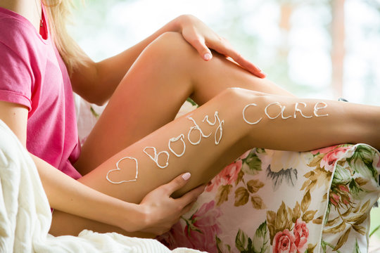 Young beautiful woman applying moisturizing lotion on body skin in armchair. Sitting in pajamas with tube of moisturizer, touching legs. Heart drawn with cream. Love your body and skin care concept.